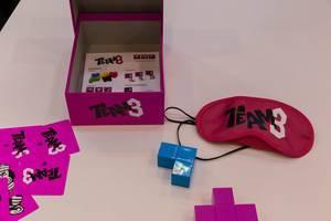 Team 3 Spiel ausgebreitet auf einem weißen Tisch mit Spielmaterial und Rollenkarten