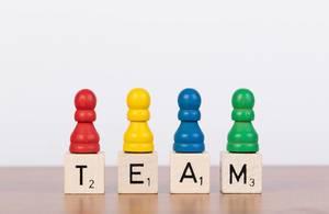 Team-Konzept mit bunten Spielfiguren und Scrabblesteinen