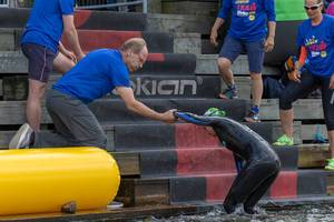 Team members of the Ironman 70.3. in Lahti helping a swimmer to get out of the water