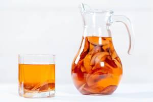 Tee aus getrockneten Früchten in Krug und Glas vor weißem Hintergrund