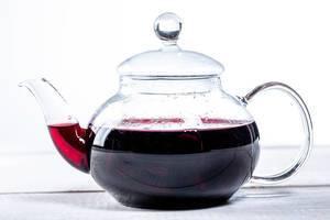 Teekanne mit  rotem Hibiskustee auf weißem Tisch