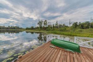 Teichlandschaft mit grünem Ruderboot auf kleinem Bootssteg