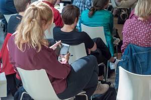Teilnehmerin schaut auf ihr Handy