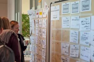 Teilnehmerinnen schauen sich den Session-Plan an. Barcamp Köln 2018