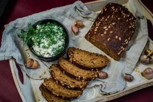 Teilweise geschnittenes dunkles Brot mit Kräuterquark und Knoblauchzehen auf Holztablett