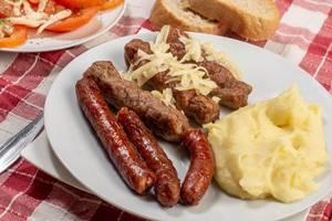 Teller mit Cevapcici aus Hackfleisch bestreut mit Käse, dazu Kartoffelbrei, Brot und Tomaten