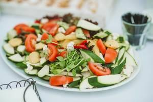 Teller mit einem frischen veganen Salat als gesunde Vorspeise, auf einem weißen Teller