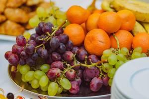 Teller mit frischen Weintrauben und Mandarinen
