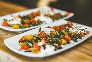 Teller mit gegrilltem Spinat und Tomaten in Sahnesauce