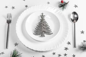 Teller mit Löffel und Gabel auf einem weißen Tisch mit Weihnachts-Silber-Dekor