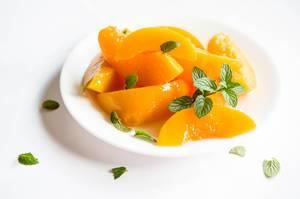 Teller mit Pfirsichscheiben und Minze