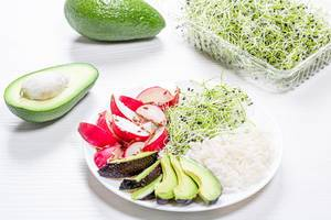 Teller mit Reis, Radieschen und Avocado als veganes Mittagessen, auf einem Küchentisch