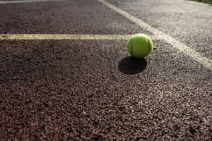 Tennisball auf dem Gummigranulat eines Tennisplatzes