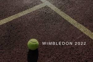 """Tennisball liegt auf der Spielfläche eines Tennisplatz neben dem Namen des Londoner Sportevents """"Wimbledon 2022"""""""