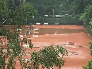 Tennisplatz im Regen überflutet.