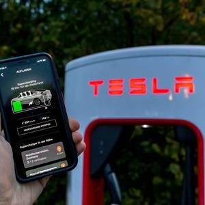Tesla Aufladen mit der Supercharging Funktionalität in der App vor einer Tesla Ladesäule