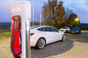Tesla Super Charger with illuminated lettering by night and white Tesla Model 3 in the background