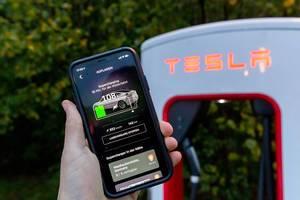 Tesla supercharging in the smartphone app held in front a Tesla charging station