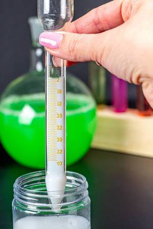 Test tube with scale and white liquid in hand (Flip 2020)