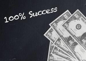 Text 100% SUCCESS (100% Erfolg) neben Banknoten auf schwarzem Hintergrund