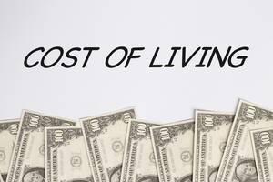 Text COST OF LIVING (Lebenshaltungskosten) auf weißem Hintergrund darunter Dollarnoten
