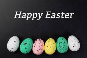 Text HAPPY EASTER (frohe Ostern) über Reihe aus bunten Ostereiern vor schwarzem Hintergrund