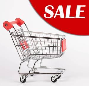 Text SALE (Sonderverkauf, Schlussverkauf) auf rot in rechter Ecke neben Einkaufswagen auf weißem Hintergrund