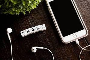 """Textwürfel zeigen das Wort """"Phone"""" - Telefon, neben einem Handy mit weißen Kopfhörern"""