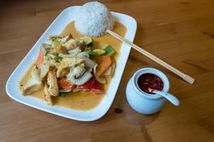 Thai Food - Rotes Vegan Curry mit Tofu, Pilzen, Zucchini, Paprika und Karotten mit geformten Reis auf einem Teller mit Bambus-Essstäbchen und Chilipaste in einem Gefäß