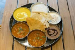 Thali Lunch - Hühnchenbrust in Kokos-Cashew-Curry serviert mit Basmati Reis, Fladenbrot, Kartoffel-Tomaten-Curry, Kichererbsen-Curry, Raita und Schokoladencreme