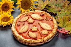 Thanksgiving Kürbiskuchen auf einem Tisch mit herbstlichen Blättern umrandet