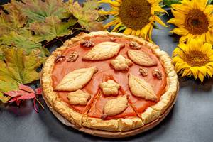 Thanksgiving pumpkin pie on a table with autumn leaves (Flip 2019)