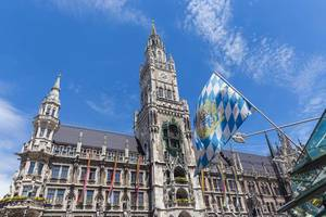 The Bavarian flag in front of rainbow flags at Marienplatz for Munich Pride, to set an example for more tolerance towards the gay community
