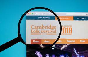 The Cambridge Folk Festival logo on a computer screen with a magnifying glass