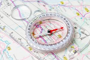The compass lies on the map. Terrain orientation concept (Flip 2020)