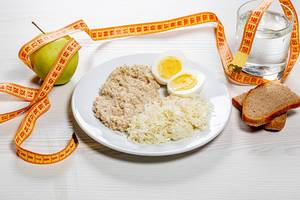 The concept of a healthy diet. Low calorie lunch with measuring tape on white wooden background