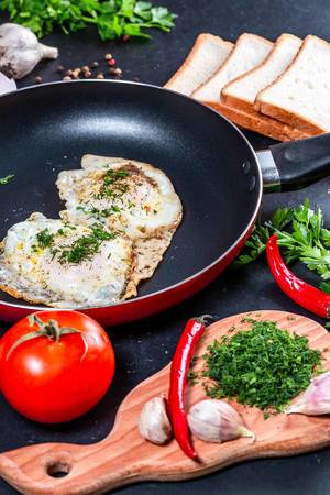The concept of cooking Breakfast-fried chicken eggs in a frying pan with slices of bread, herbs and vegetables (Flip 2019)