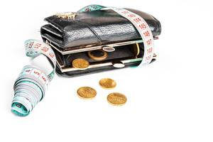 The concept of crisis, lack of money, loss of financial stability - wallet with coins and a measuring tape