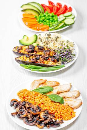 The concept of delicious healthy food. Baked eggplant with couscous, chicken with mushrooms and chickpeas and vegetable slicing (Flip 2019)
