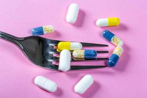 The concept of drug nutrition-encapsulated medicines with a fork on a pink background
