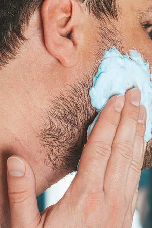 The concept of facial care for men. A man applies shaving gel to his face (Flip 2019)
