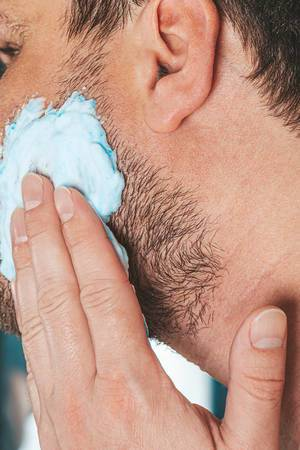 The concept of facial care for men. A man applies shaving gel to his face
