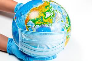 The concept of the fight against respiratory diseases. Gloved hands hold a globe and a medical mask on a white background
