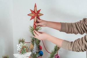 The girl puts a star on the top of the Christmas tree