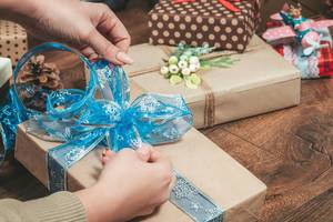 The girl ties a bow on the gift box. The concept of preparing for Christmas
