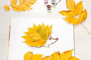 The hedgehog is made of autumn yellow leaves with foliage and paints on a white wooden table (Flip 2019)