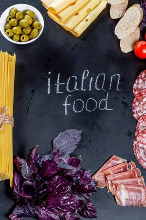 "The inscription ""Italian food"" on a black background with a frame of products of Italian cuisine"