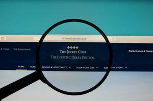 The Jockey Club logo on a computer screen with a magnifying glass