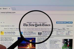 The New York Times logo on a computer screen with a magnifying glass