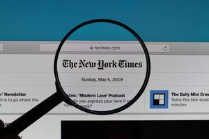 The New York TImes logo under magnifying glass